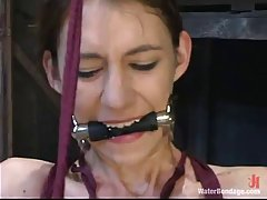 Gagged babe in latex costume is tied up tight and stimulated with sex toys and water