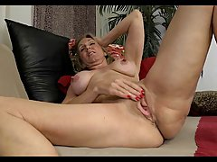 Blonde mature with big tits is rubbing her moistened slit and moaning from pleasure while doing it