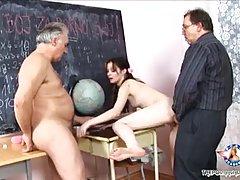 Petite schoolgirl is kneeling in the classroom and sucking dick while her teacher is watching