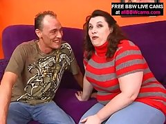 Fat woman is sucking dick and rubbing her pussy on a purple couch, at the same time