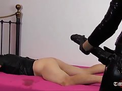 Dominant lady in latex outfit is drilling her sex slave's ass with a huge, black dildo