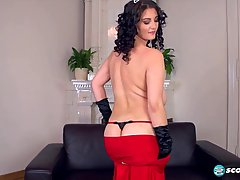 Big titted brunette in red dress is masturbating on the couch, in front of the camera