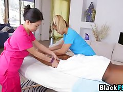 Two girls are giving a special massage to a handsome, black guy and enjoying it a lot