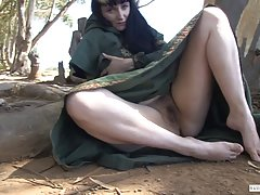 Dark haired lady dressed up as an elf is spreading her legs wide and fingering her pussy